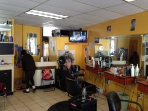 """El interior de la peluquería """"M and S;"""" al fondo Miriam usa una escoba"""
